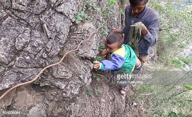 Chen Guji holds the safety belt on his sixyearold son Chen Muhei in passing a nopath on a cliff on their way home in Zhaojue county in southwest...