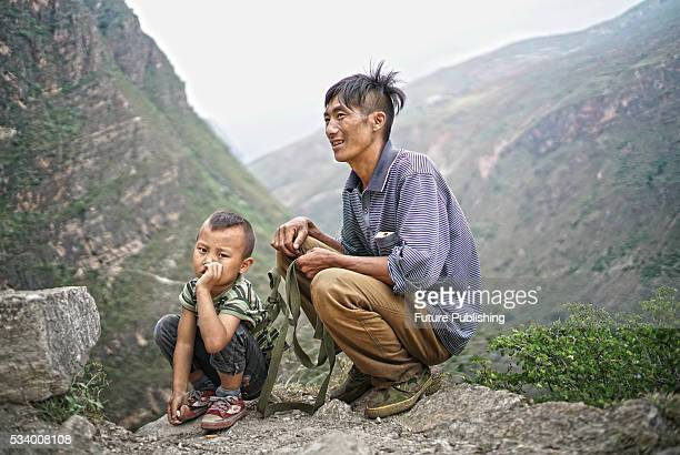Chen Guji puts the safety belt on his sixyearold son Chen Muhei on their rocky way to home in Zhaojue county in southwest China's Sichuan province on...