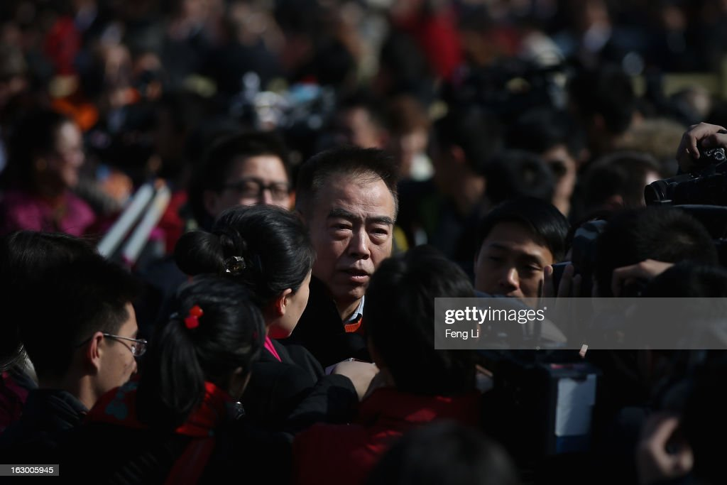 Chen Kaige (Center) , Chinese famous film director, walks through a swarm of journalists outside the Great Hall of the People before the opening session of the Chinese People's Political Consultative Conference on March 3, 2013 in Beijing, China. Over 2,000 members of the 12th National Committee of the Chinese People's Political Consultative, a political advisory body, are attending the annual session, during which they will discuss the development of China.