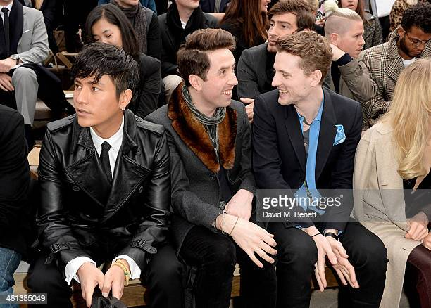 Chen Kun Nick Grimshaw and George Barnett sit in the front row during the Burberry AW14 Menswear Show at Kensington Gardens on January 8 2014 in...