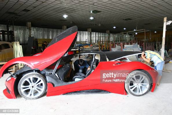 Chen Yinxi the owner of the electriccar works on his car in a glass factory owned by his father on July 17 2015 in Haikou in south China's Hainan...