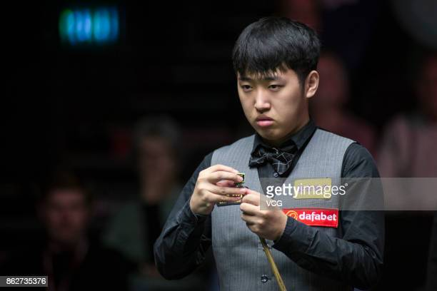 Chen Zifan of China chalks the cue during his second round match against Barry S Hawkins of England on day three of 2017 Dafabet English Open at...