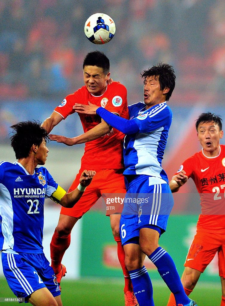 Chen Zijie (2L) of China's Guizhou Renhe tussles for the ball against Park Dong-hyuk (2R) of South Korea's Ulsan Hyundai during their AFC Champions League group H first round match at the Guiyang Olympic Centre Stadium, in Guiyang, Guizhou province on April 1, 2014. Renhe beat Ulsan 3-1. CHINA OUT AFP PHOTO