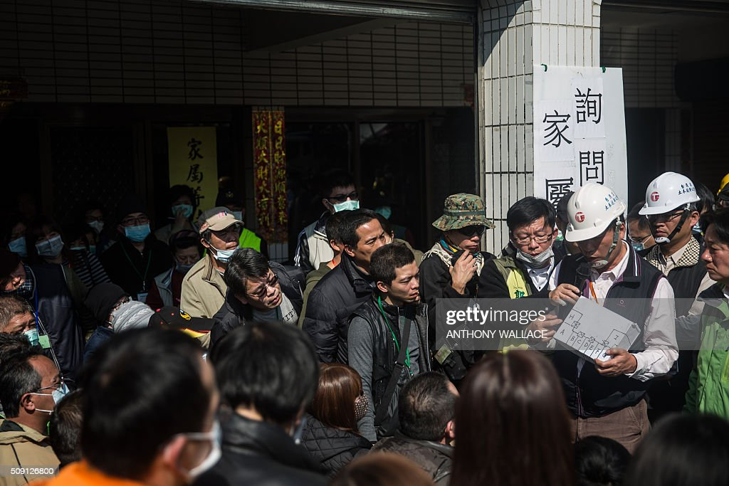 Cheng Ming-chang (holding object) president of Tainan Civil Engineers Association uses a diagram as he and Tainan's Mayor William Lai (far R, in green) brief relatives on the rescue operation of a building which collapsed in the 6.4 magnitude earthquake, as in the southern Taiwanese city of Tainan on February 9, 2016. Rescuers deployed heavy machinery on February 9 in a renewed effort to locate more than 100 people trapped in the rubble of a Taiwan apartment complex felled by an earthquake as the 72-hour 'golden window' for finding survivors passed. AFP PHOTO / ANTHONY WALLACE / AFP / ANTHONY WALLACE