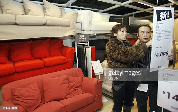A couple checks the price tag next to the sofas displayed at the newlyopened Ikea store in China's west Chengdu 29 November 2006 Swedish furniture...