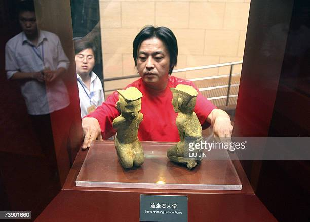 A musuem staff places the two stone sculptures of kneeling human figure for display prior to the opening of the Jinsha Museum in Chengdu southwest...