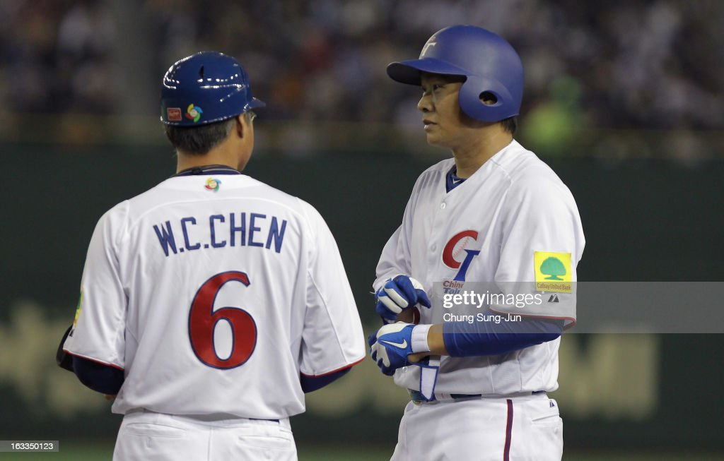 Cheng-Min Peng # 23 of Chinese Taipei talks with coach Wei-Cheng Chen # 6 after hits a RBI single in the fifth inning during the World Baseball Classic Second Round Pool 1 game between Japan and Chinese Taipei at Tokyo Dome on March 8, 2013 in Tokyo, Japan.