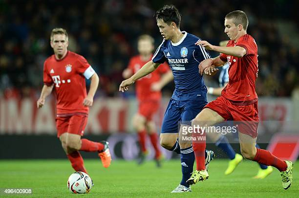 Chengyou Jin of Paulaner Traumelf and Gianluca Gaudino of Muenchen compete for the ball during the friendly match between FC Bayern Muenchen and...