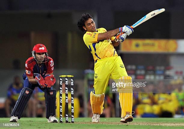 Chennai Super Kings batsman MS Dhoni knocks a ball to the boundary as Delhi Daredevils wicket keeper Naman Ojha looks on during the IPL Twenty20...