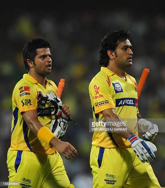 Chennai Super Kings batsman Suresh Raina and captain Mahendra Singh Dhoni walk off the field after their innings during the IPL Twenty20 cricket...