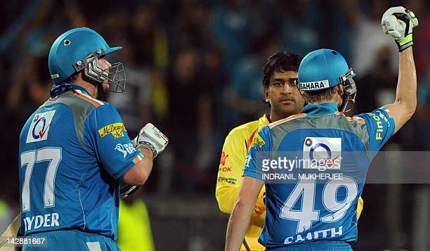 Chennai Super Kings captain Mahendra Singh Dhoni looks on as Pune Warriors India batsmen Steven Smith and Jesse Ryder celebrate after scoring the...