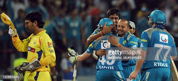 Chennai Super Kings captain Mahendra Singh Dhoni walks away as Pune Warriors India cricketers greet teammates Steven Smith and Jesse Ryder celebrate...