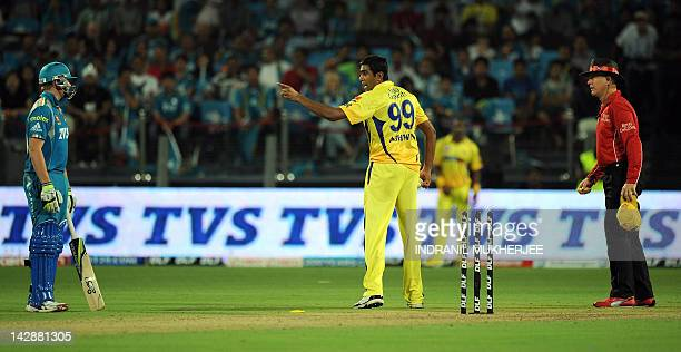 Chennai Super Kings cricketer Ravichandran Ashwin exchanges words with Pune Warriors India batsman Steven Smith as umpire Bruce Oxenford of Australia...