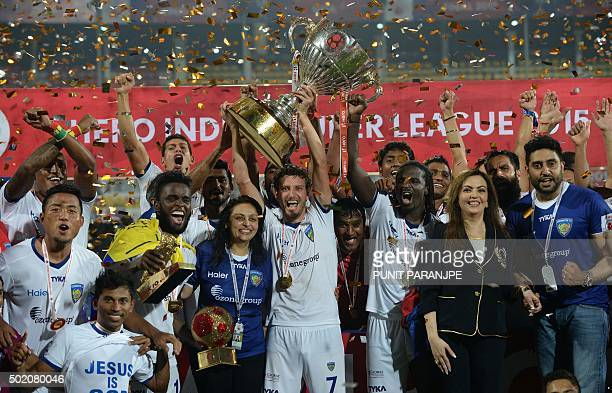 Chennaiyin FC players pose with the trophy as they celebrate along with Bollywood actor Abhishek Bachchan and Nita Ambani after winning the final...