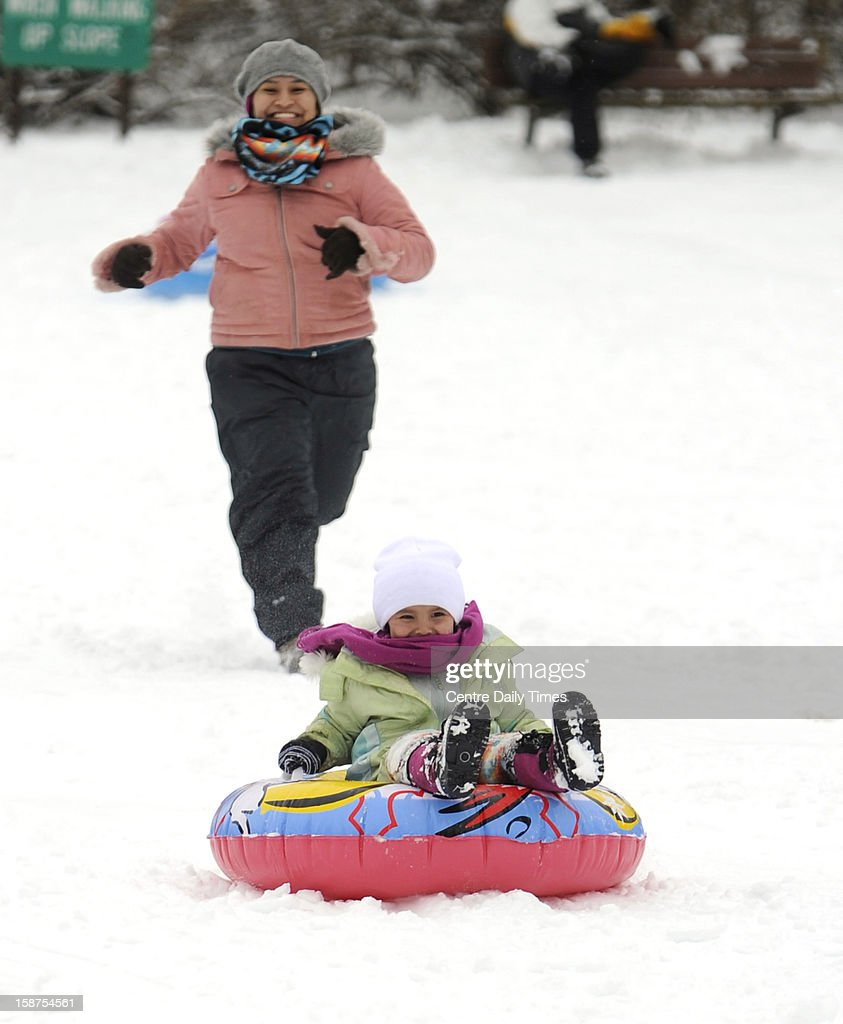 Chenoa Begaye, left, chases her daughter Dallsye Begaye, 4, down the hill at Slab Cabin Park in State College, Pennsylvania, Thursday, December 27, 2012.
