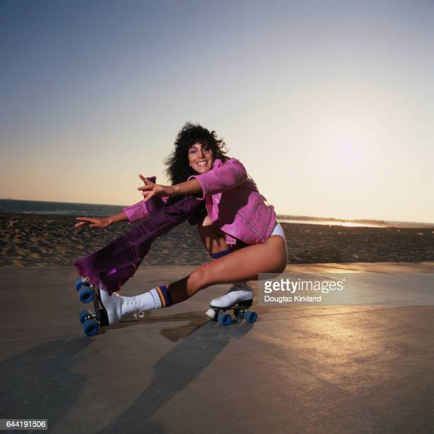 Cher wearing a pink leather jacket and white swimsuit shows off her roller skating moves at Venice Beach