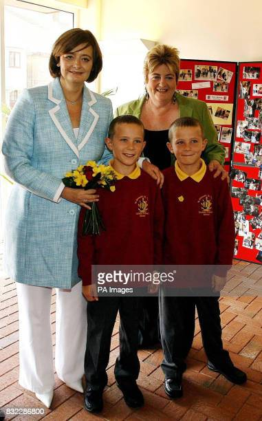 Cheri Blair is presented with flowers by twin brothers Jamie and Daniel Howard on a visit to her old primary school St Edmund's and St Thomas...
