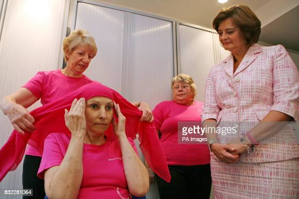 Cherie Booth wife of British Prime Minister Tony Blair and Patron of Breast Cancer Care watches as Headstrong volunteer Val Clegg left ties a head...