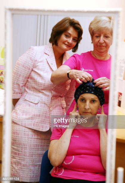 Cherie Booth wife of British Prime Minister Tony Blair and Patron of Breast Cancer Care watches in a mirror as Val Clegg demonstrates hat styles for...