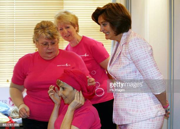 Cherie Booth wife of British Prime Minister Tony Blair and Patron of Breast Cancer Care watches as Headstrong volunteer Chris Lockwood ties a head...