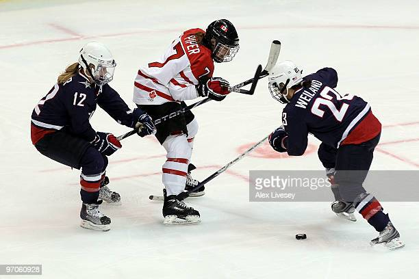 Cherie Piper of Canada is closed down by Jenny Potter and Kerry Weiland of the United States during the ice hockey women's gold medal game between...