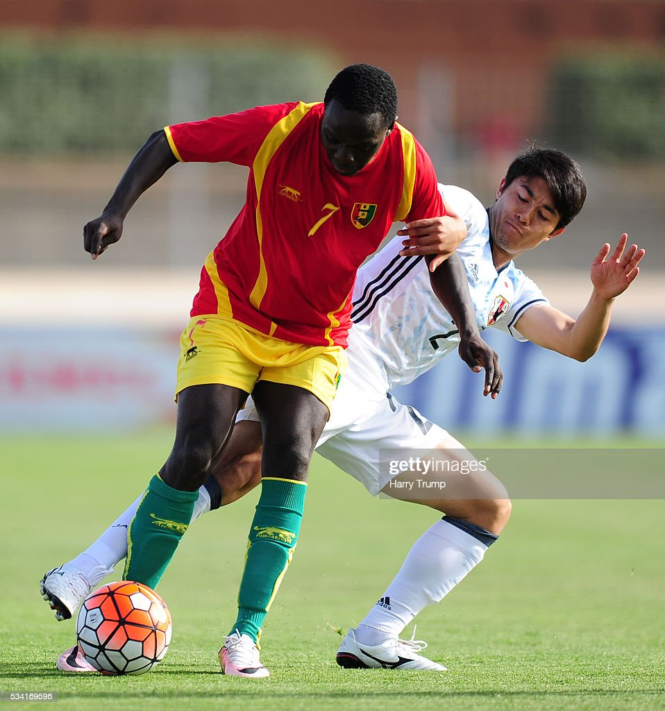 Cherif Tasfir of Guinea is tackled by Sai Van Vermeskerken of Japan during the Toulon Tournament match between Guinea and Japan at Stade Antoinr Baptiste on May 25, 2016 in Six-Fours-Les-Plages, France.