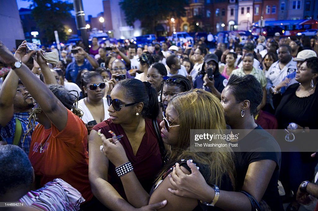 Cherita 'Cookie' Whiting, front C, Chuck Brown's daughter, makes her way through the crowd where hundreds of people gather outside the Howard Theatre in honor of legendary go-go godfather Chuck Brown on May 16, 2012, in Washington, DC. At 75-years-old, Chuck Brown died today.