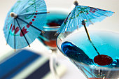 Cherries on end of mini cocktail umbrellas in drinking glasses containing blue curacao
