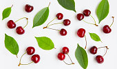 Cherry background. Composition of red cherry berries and green leaves on white background, close up. Beautiful Food Wallpaper or Web banner. Top view. Flat lay.