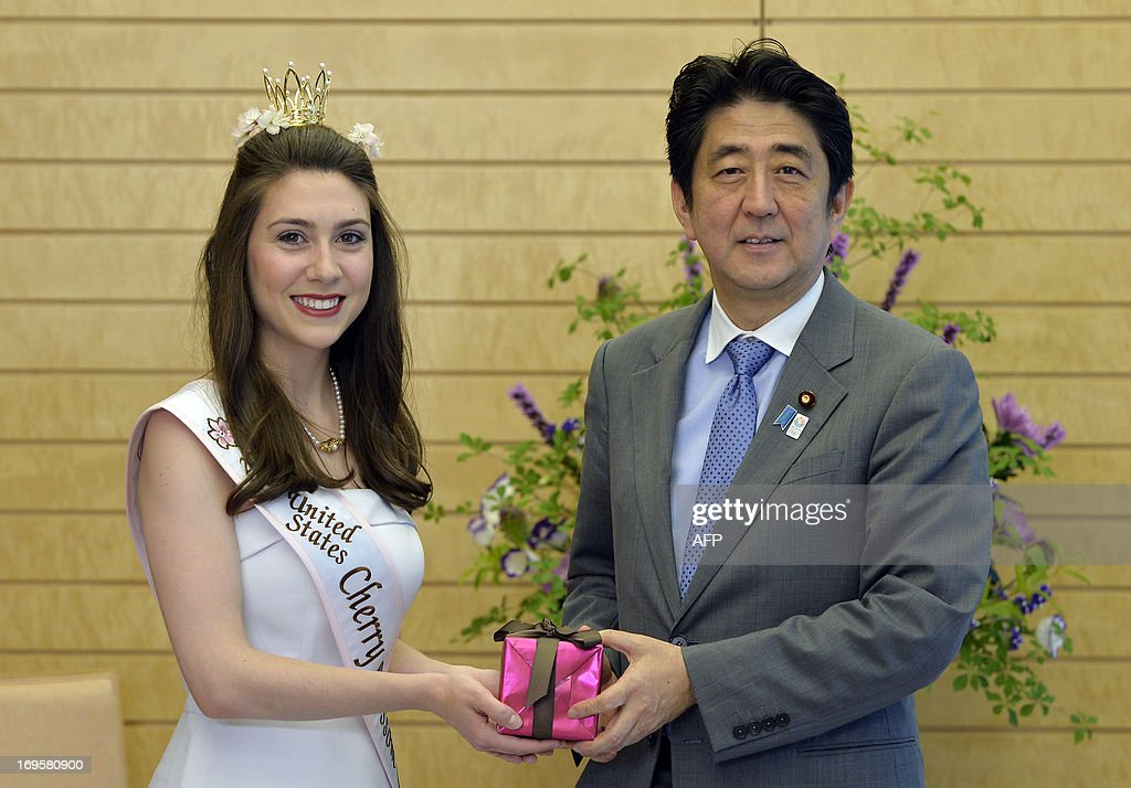 US Cherry Blossom Queen Mary Anne Morgan (L) from Oklahoma gives a present to Japanese Prime Minister Shinzo Abe (R) during a courtesy call at the prime minister's official residence in Tokyo on May 28, 2013. Morgan won the title in April and is serving as a goodwill ambassador to Japan.