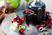 Cherry homemade liquor in a vintage bottle on a wooden background with fresh cherries.