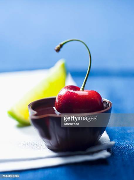 A cherry in alcohol in a tiny bowl made of chocolate