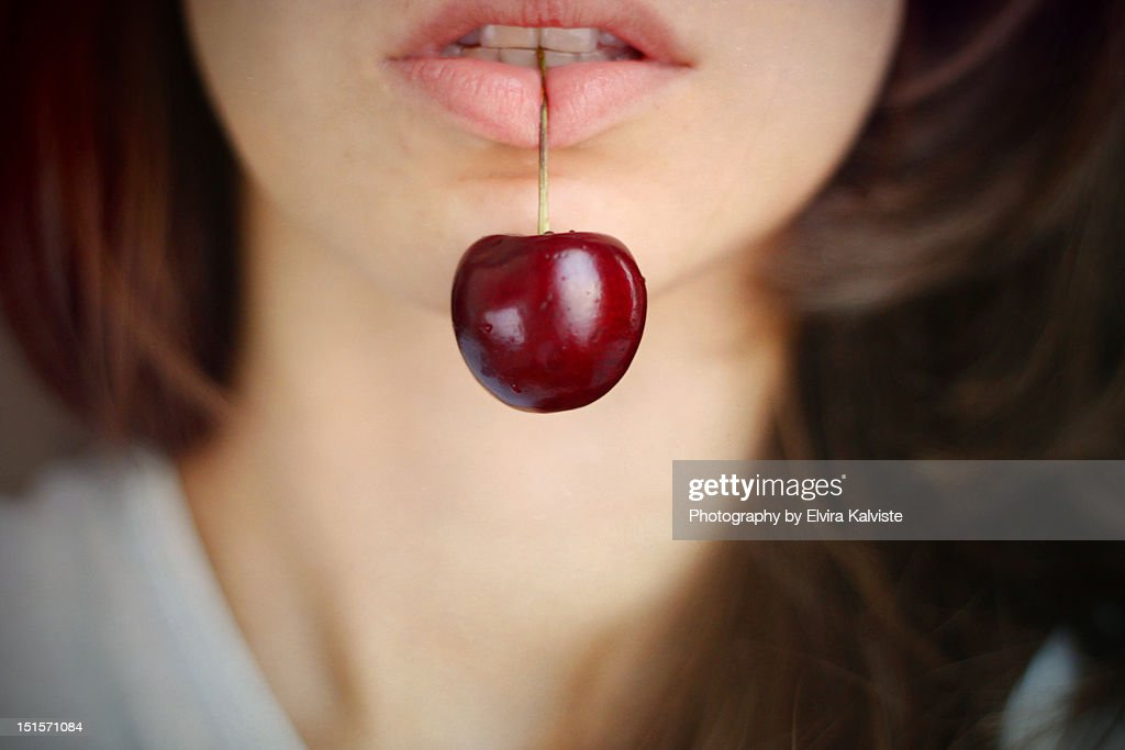 Cherry in girl's mouth : Stock Photo