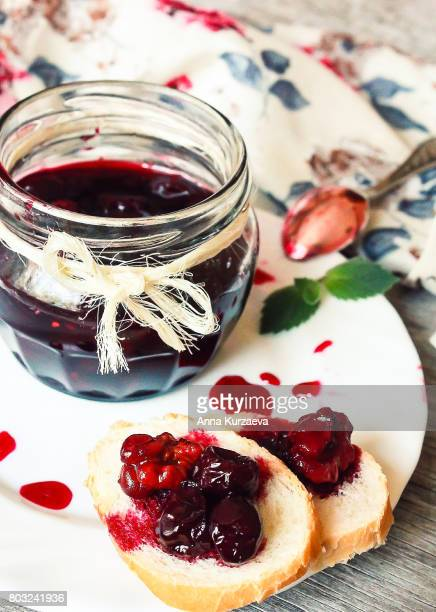 Cherry jam or marmalade with walnuts in a jar, selective focus