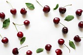 Colourful bright pattern with ripe cherry and leaf. Top view.