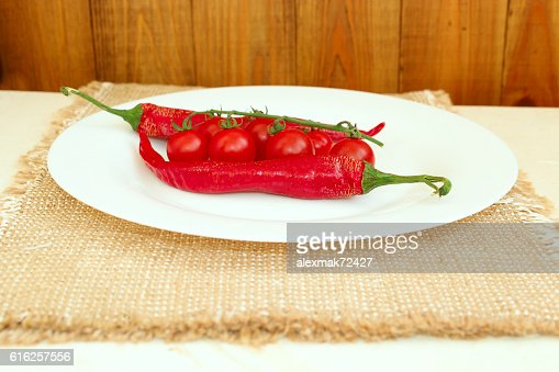 cherry tomatoes and pods of chili peppers on the plate : Foto de stock