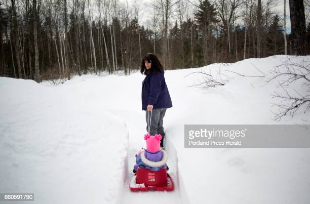 Cheryl Baker pulls her granddaughter Claire Smith in a sled down to the chicken coop to collect that day's eggs