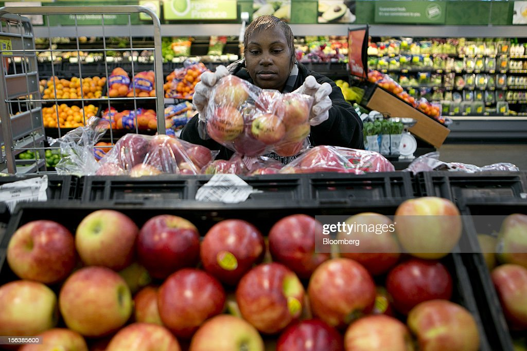 Cheryl Berryhill stocks apples at a Wal-Mart store in Alexandria, Virginia, U.S., on Wednesday, Nov. 14, 2012. Wal-Mart Stores Inc. is scheduled to release earnings data on Nov. 15. Photographer: Andrew Harrer/Bloomberg via Getty Images