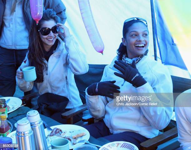 Cheryl Cole and Alesha Dixon smile as they have supper in their tent on the second day of The BT Red Nose Climb of Kilimanjaro on March 1 2009 in...
