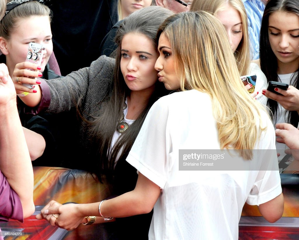 Cheryl Cole poses with a fan as she arrives for the Manchester auditions of The X Factor at Lancashire County Cricket Club on June 16 2014 in...