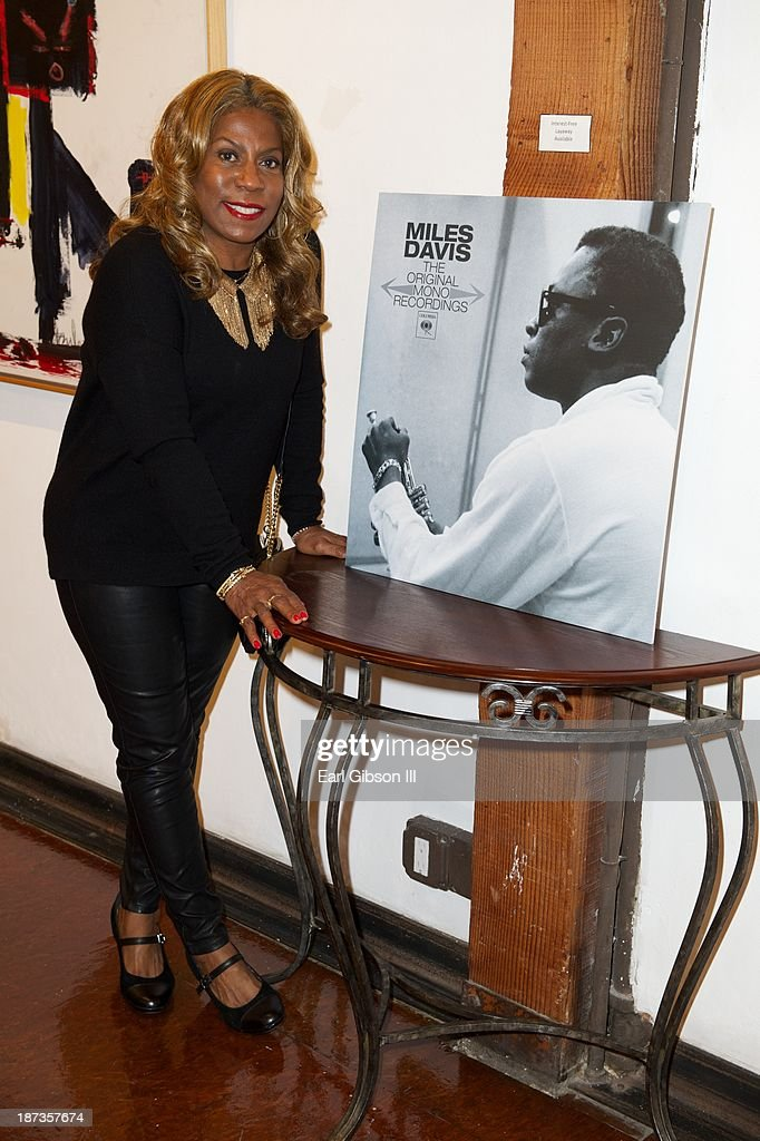 Cheryl Davis (daughter of Miles Davis) poses next to a photo of her father at the Miles Davis Collected Artwork Launch Party at Mr. Musichead Gallery on November 7, 2013 in Los Angeles, California.