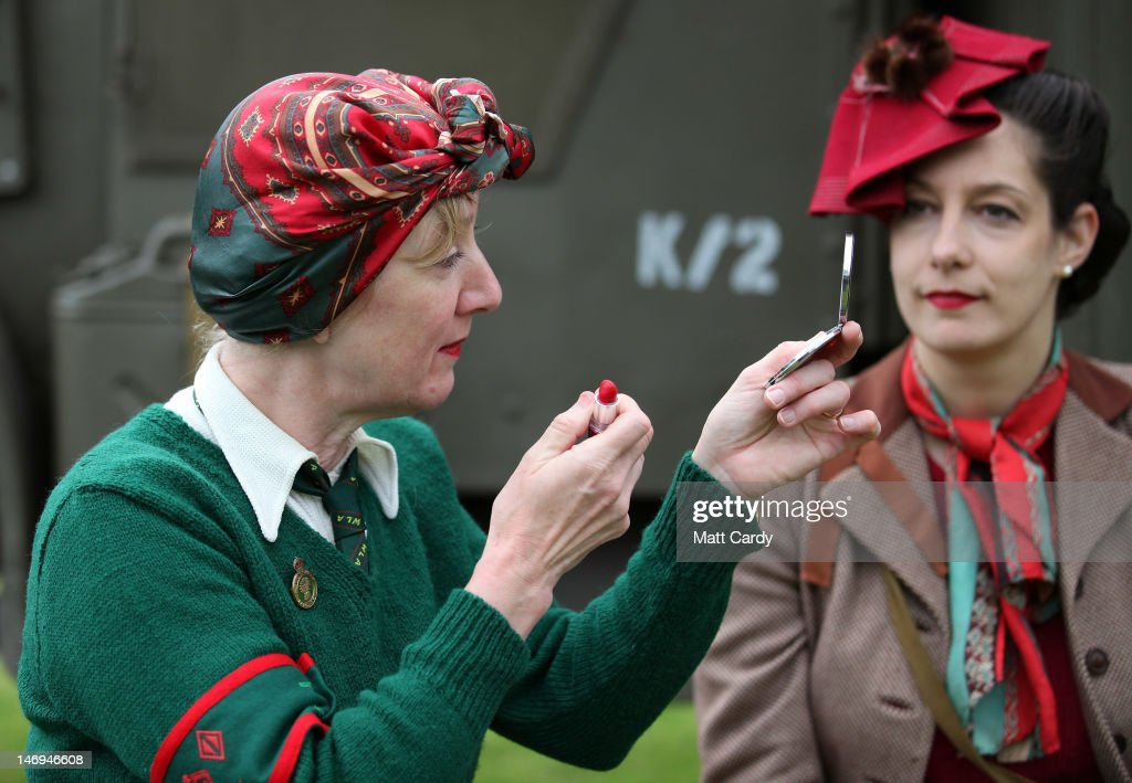 Cheryl Ludgate (L) checks he lipstick as she dresses as a land girl from the Women's Land Army as she chats to Naomi White (R) as part of the two-day Maiden Newton At War 1940s re-enactment weekend in Maiden Newton on June 23, 2012 near Dorchester, England. The quiet Dorset village of Newton Maiden was seen as a strategic hub during the Second World War and was heavily fortified against a threatened German invasion. It later saw hundreds of American servicemen quartered in the area before the D Day landings. To celebrate the village's wartime past, the biennial event, which started in 2008, has grown into one of the biggest re-enactments in the country and this year featured one of the largest convoys of Second World War vehicles seen in Dorset since D Day in 1944.