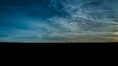 Dark and Moody Image of People Silhouetted at Chesil Beach