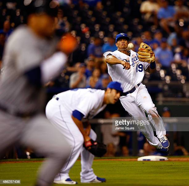 Cheslor Cuthbert of the Kansas City Royals throws out Victor Martinez of the Detroit Tigers as pitcher Scott Alexander ducks during the 9th inning of...