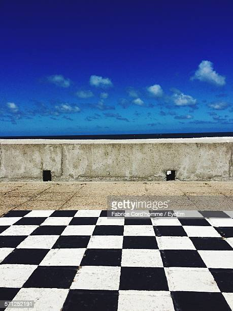 Chess Board Pattern On Floor In Front Of Sea Against Blue Sky