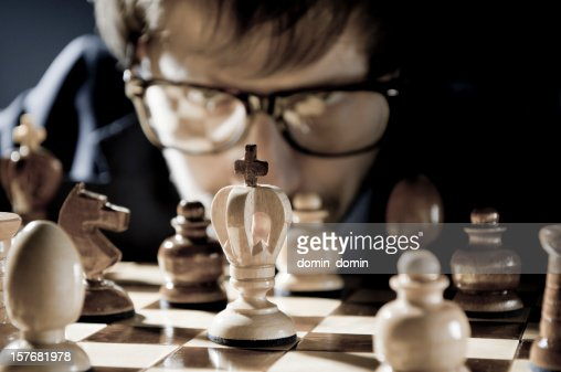 Chess competition, player in glasses thinking about next move