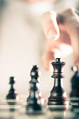 Vertical Image of a chess game with focus on the queen and a blurry hand at the background, Copy space on the left side. Concept of strategic business or risk management.