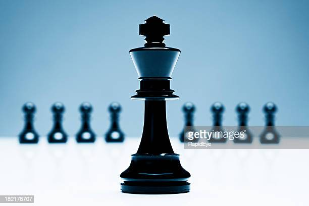Chess king stands in front of  pawns, leading the pack