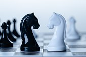 Black and white chess knights face to face