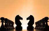 Silhouettes of knights chess pieces surrounded by pawns